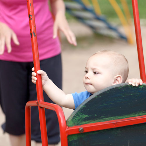 Young toddler playing on swing