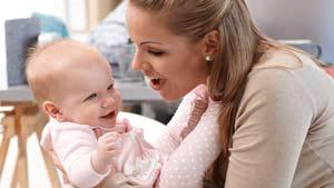 Mum holing giggling baby girl