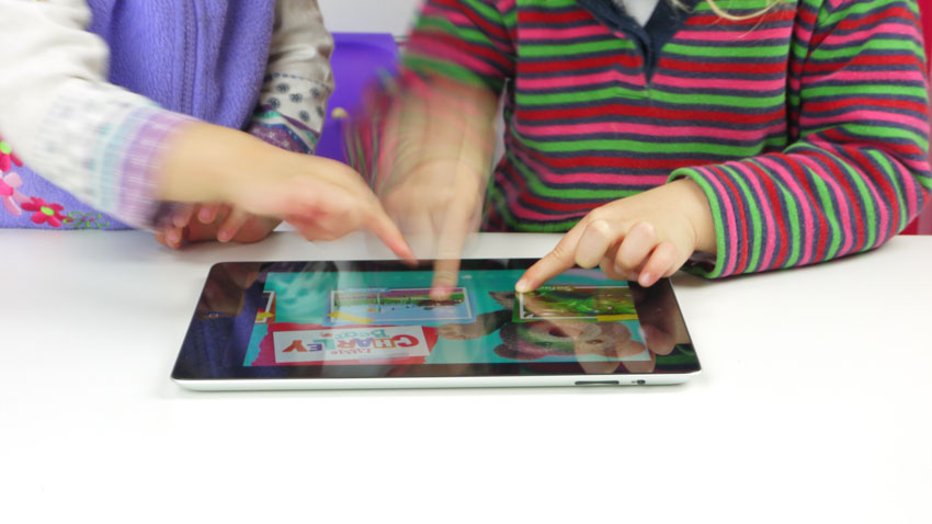 2 toddlers touching tablet screen